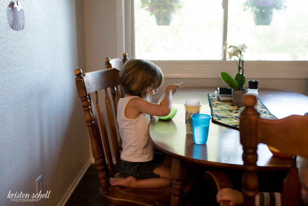 Set in the dining room. You'll see a little 4 year old girl on a chair eating her cereal out of a green bowl. There are cups in the foreground and a plant in the background.