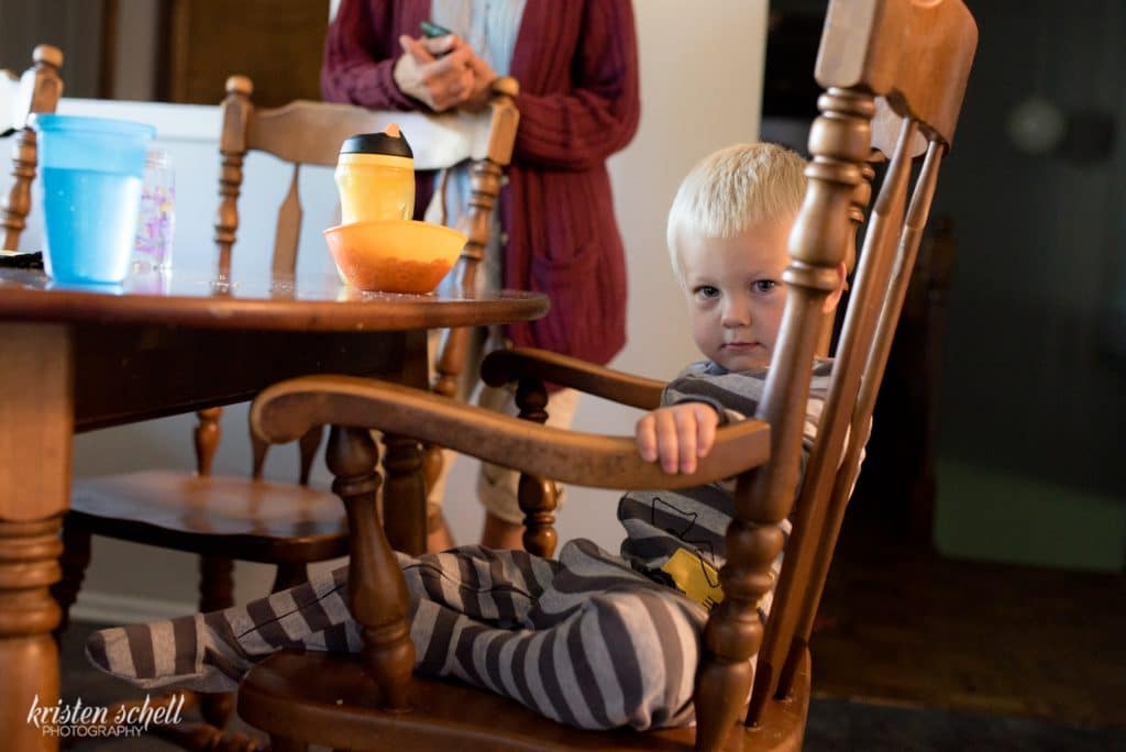In the dining room, there is a two year old boy wearing a light and dark gray stripe sleeper. He is sitting on a brown chair. He is looking straight at the camera. His face looks curious.