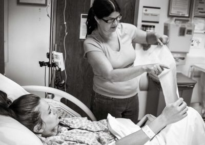 Pregnant woman is laying on the bed looking at the paper printout of the contractions. A former labor and delivery nurse is standing next to her holding up the printout and she is explaining what it means.