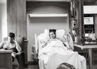 Wide shot of a hospital room. Pregnant woman is resting on the bed. While her husband is sitting on a chair next to her. He is on his smartphone.