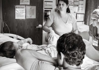 Pregnant woman is on the hospital bed. She is in a pushing position to deliver her baby.