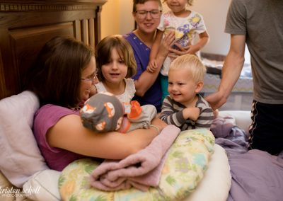 Mom is holding newborn baby while older brother and sister is looking at newborn and smiling. They are on the bed.