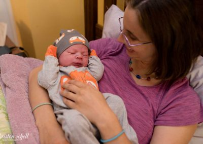 Mom is resting in bed. She is holding her newborn baby boy who is wearing a gray onesie with a fox. He is wearing a matching hat. He is sleeping with his arms up. HIs mom is looking at him and smiling. This is at a home birth and newborn lifestyle session.
