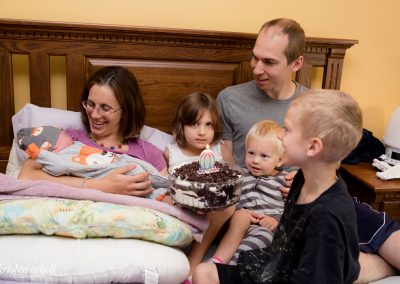 Mom is holding newborn while her husband, daughter and other two sons are on the bed with her singing a happy birthday song.