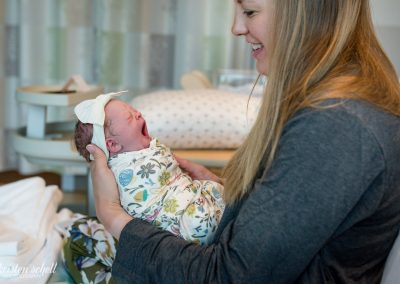 Newborn in a floral swaddle and white headband bow is yawning. She is being held by her home who is looking her smiling. She has long brown hair and is wearing a dark gray robe.