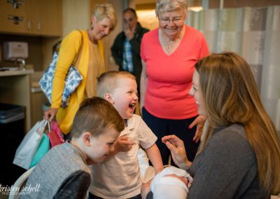 Older brother has a facial expression of joy and laughter looking at his mom who is also smiling. She is holding newborn baby sister. Grandparents are in the background looking at the brothers and smiling.