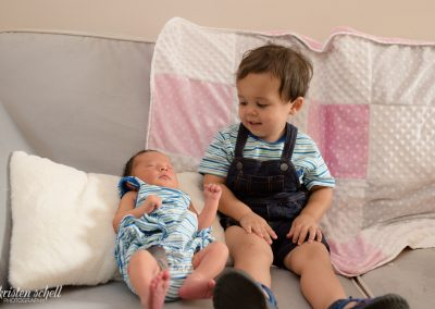 Toddler older sibling is sitting on a light gray couch with his newborn sister. He is looking at her and smiling. Newborn is laying back on a pillow and sleeping.