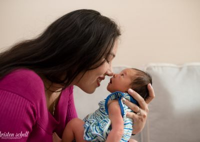 Mom with long dark brown hair is wearing a fuchsia dress. She is holding her newborn in a way that their noses are touching. The newborn is wearing a stripped blue and white dress.